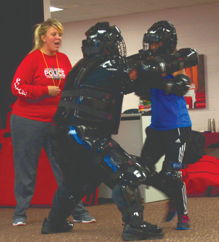 Officers Joy Paquette and James Wing instruct a female participant during the two-day Rape Aggression Defense class. Sgt. Wing and students dress in full protective gear as they practiced defense tactics.  Photo By: Melanie Ronquillo   Photographer