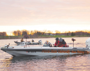 Members of the Ferris State Fishing Club brave the cold in an early morning tournament out on the lake.