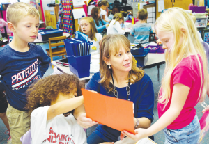 Kindergarten teacher Teresa Reaugh, center, works with her students, in her classroom on Oct. 28, 2014, at Holly Ridge Elementary School in Holly Springs, N.C. FSUS is the Kindergarten of college.